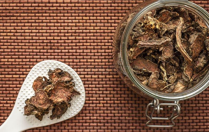 Ra?z seca cortada del rosea de Rhodiola en un tarro de cristal en fondo blanco natural imagenes de archivo