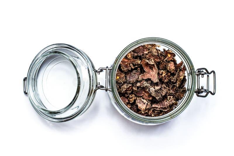 Ra?z seca cortada del rosea de Rhodiola en un tarro de cristal en fondo blanco natural foto de archivo libre de regalías