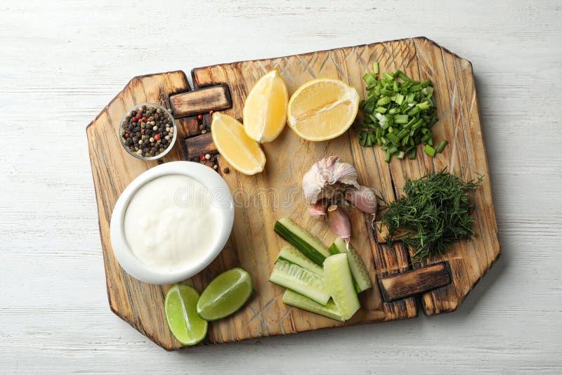 Raad met komkommersaus en ingrediënten op houten achtergrond royalty-vrije stock foto's