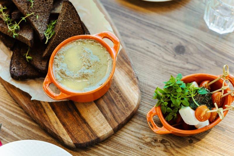 Raad met roggecrackers met rozemarijn, eigengemaakte leverpastei en een plaat met kaas, verse kersentomaten en micro- greens royalty-vrije stock afbeelding