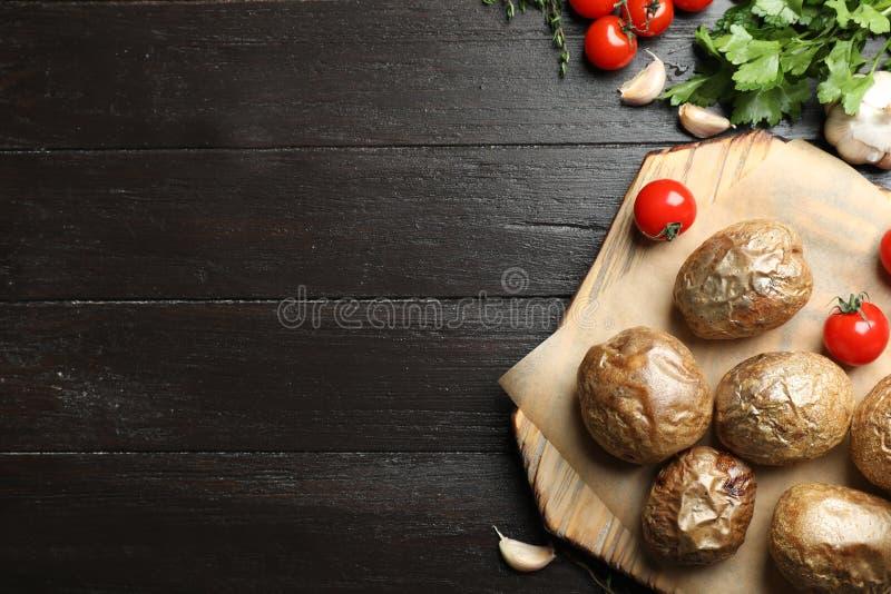 Raad met smakelijke gebakken jasjeaardappels op houten achtergrond, hoogste mening stock afbeeldingen