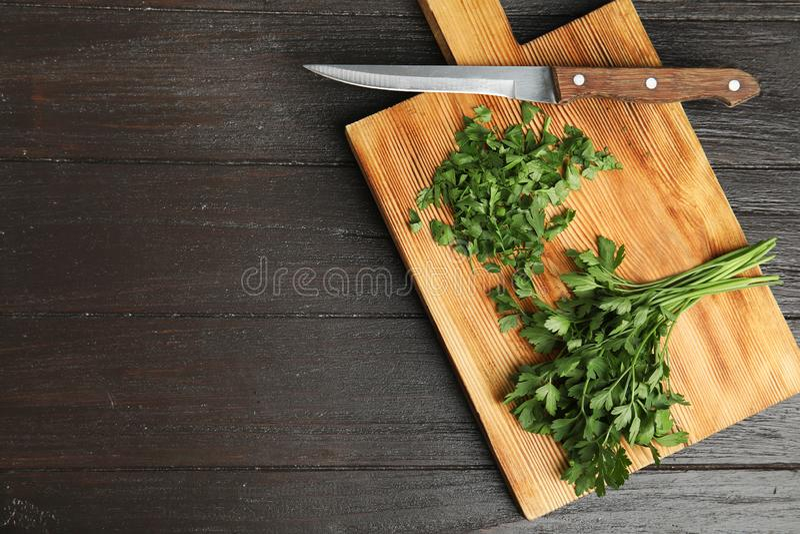 Raad met verse groene peterselie en mes op houten achtergrond, hoogste mening royalty-vrije stock fotografie
