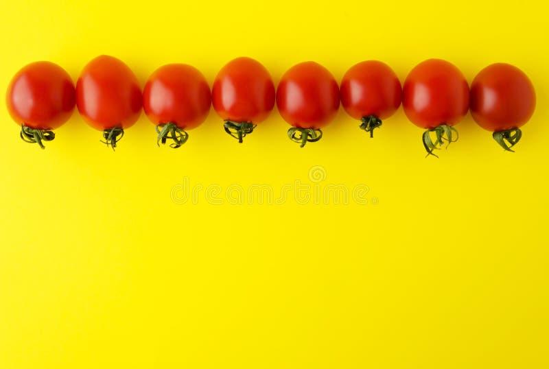 Raad met verse kersentomaten wordt gemaakt op gele baclground die Heldere kleuren van voedselontwerp stock afbeeldingen