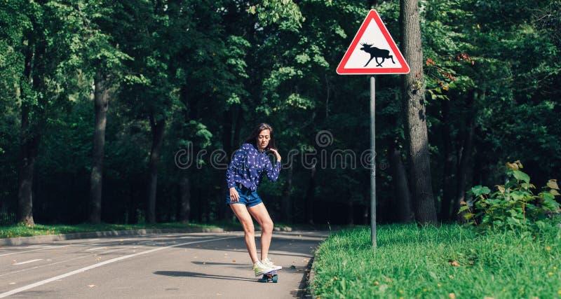 Raad van de meisjes de schaatsende stuiver in het midden van asfaltweg in het park royalty-vrije stock afbeelding