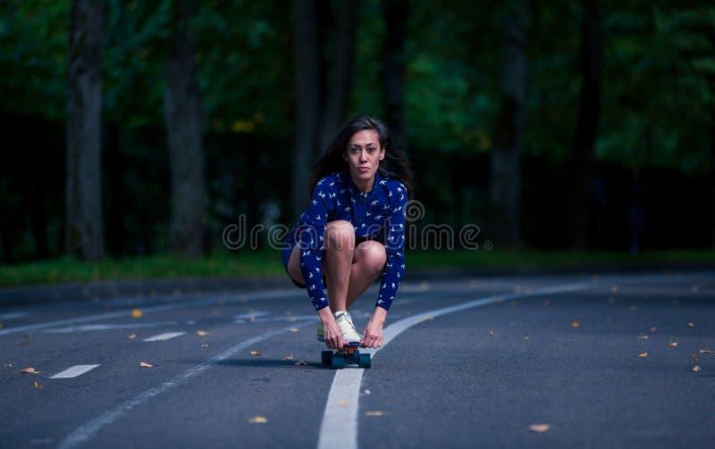 Raad van de meisjes de schaatsende stuiver in het midden van asfaltweg in het park royalty-vrije stock foto