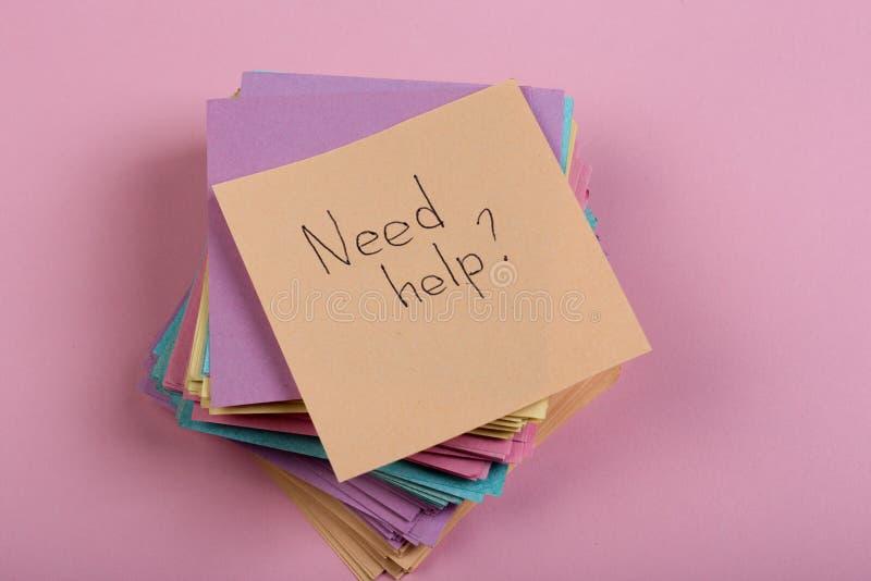 Raadsconcept - Sticker met de woorden ' behoefte help' op roze achtergrond Concept het vragen om hulp stock foto's