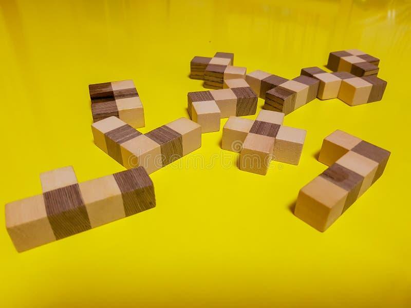 Raadselstuk van hout over gele lijst stock fotografie