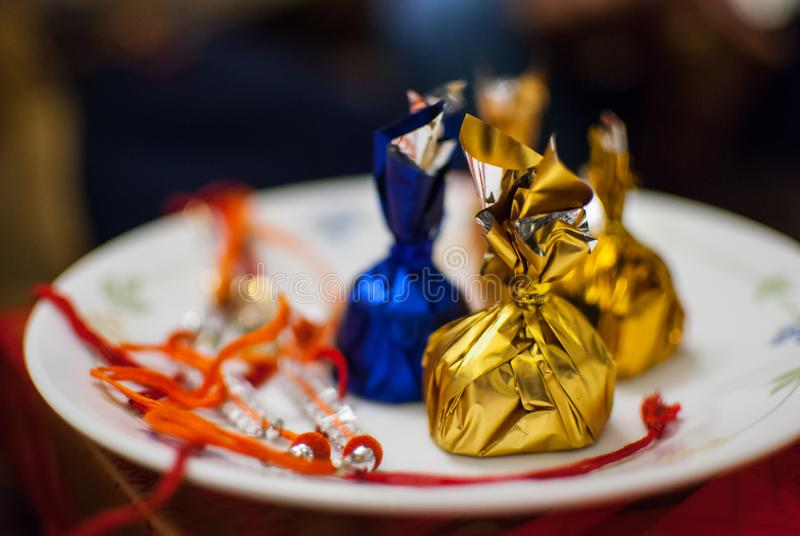 Raakhi with assorted chocolates in a plate royalty free stock photos