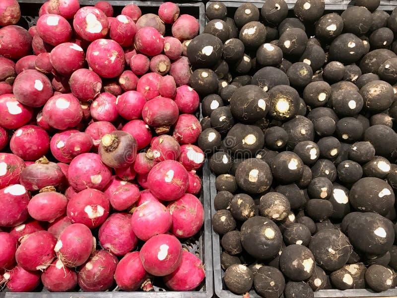 Rabanete e nabo pretos para a venda no verdureiro Market fotografia de stock