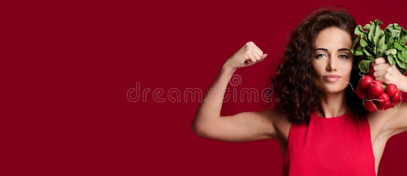 Rabanete fresco da posse nova consideravelmente alegre da mulher do esporte com folhas do verde e dedo apontar dieting fotos de stock royalty free