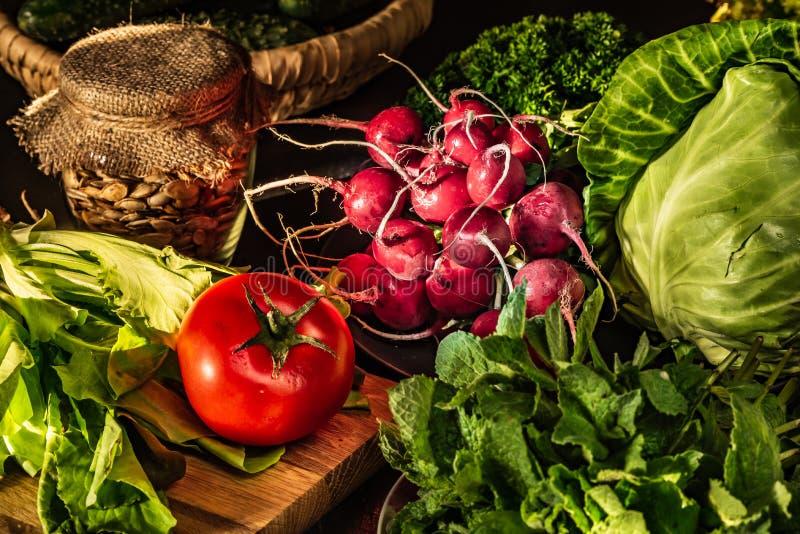 Rabanete vermelho, tomate, couve, alface e erva-cidreira na tabela Alimentos do vegetariano fotografia de stock