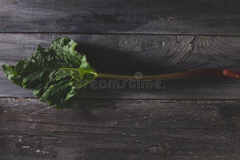 Rabarbaro fresco sulla vecchia, tavola di legno grigia immagini stock