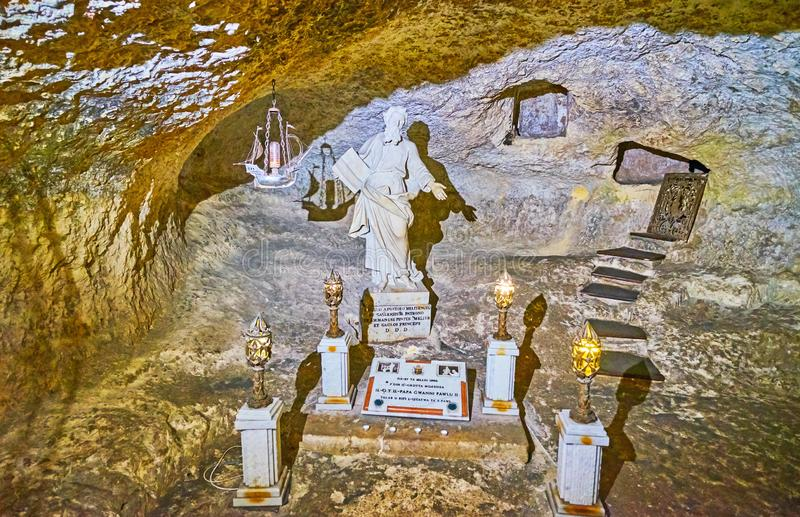 The ancient St Paul Grotto, Rabat, Malta. RABAT, MALTA - JUNE 16, 2018: Interior of famous St Paul Grotto with statue of the saint and grave niches on the royalty free stock photo