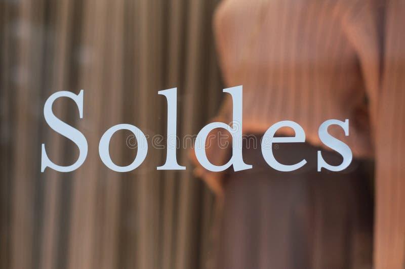 Rabattzeichen 'SOLDES 'auf Französisch, den Traduction von Verkäufen auf Fenster im französischen Modespeicher stockfotos