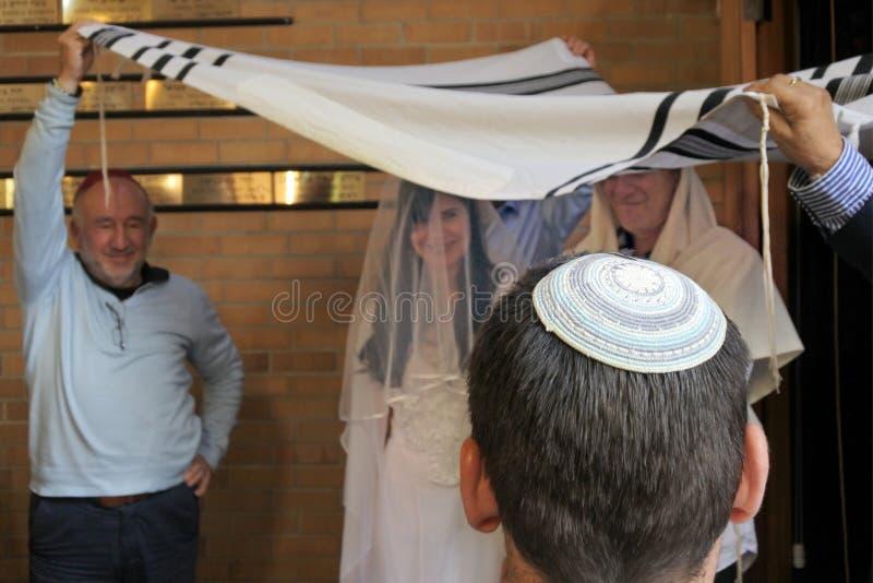Rabbin belssing la jeune mariée juive et un jeune marié sous un chupa photographie stock libre de droits