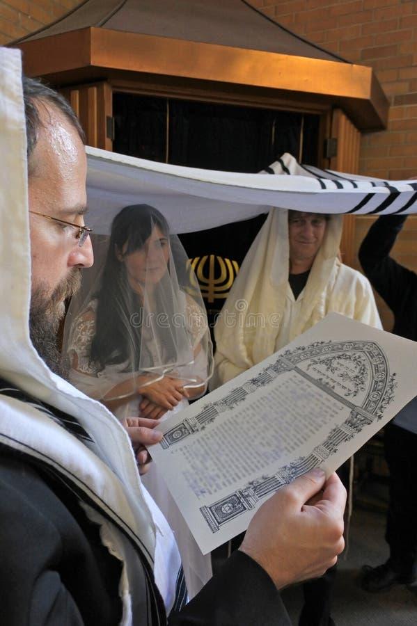 Rabbin lit l'accord prénuptial d'une jeune mariée juive et d'un bri images libres de droits