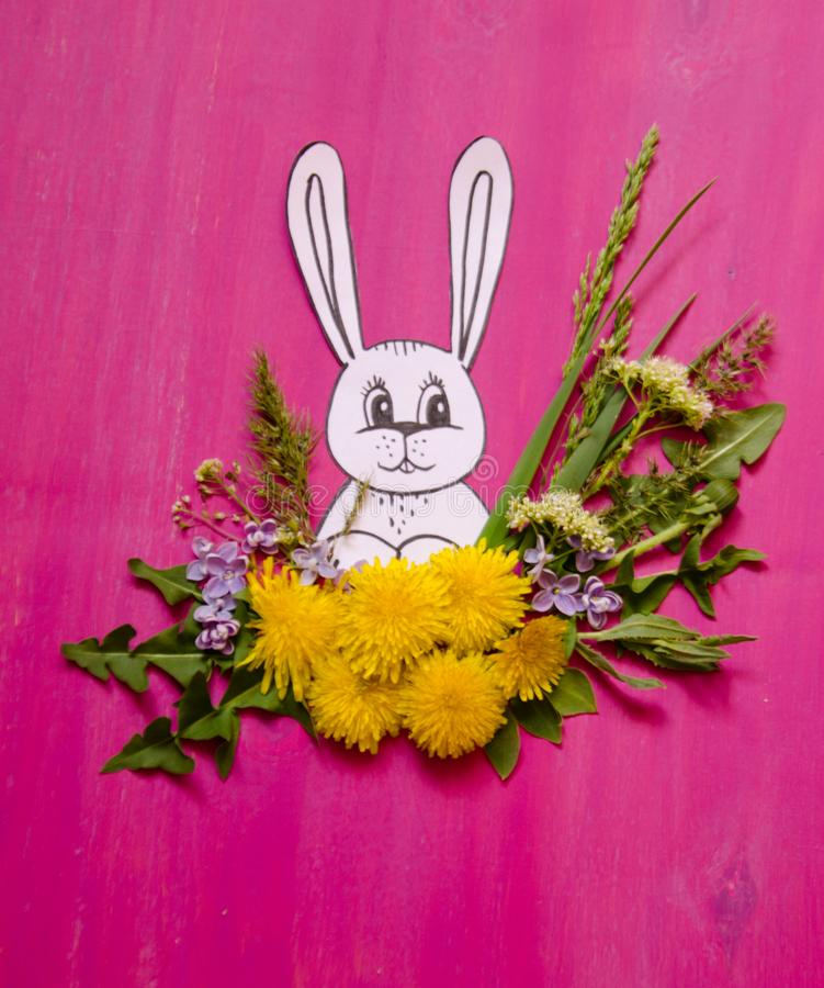 Rabbit in a bouquet of grass and dandelions flowers royalty free stock photo