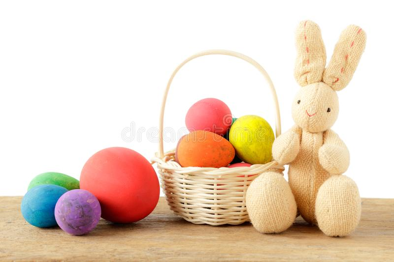 Rabbit doll with Easter eggs in basket on wooden table and isolated white background. stock image