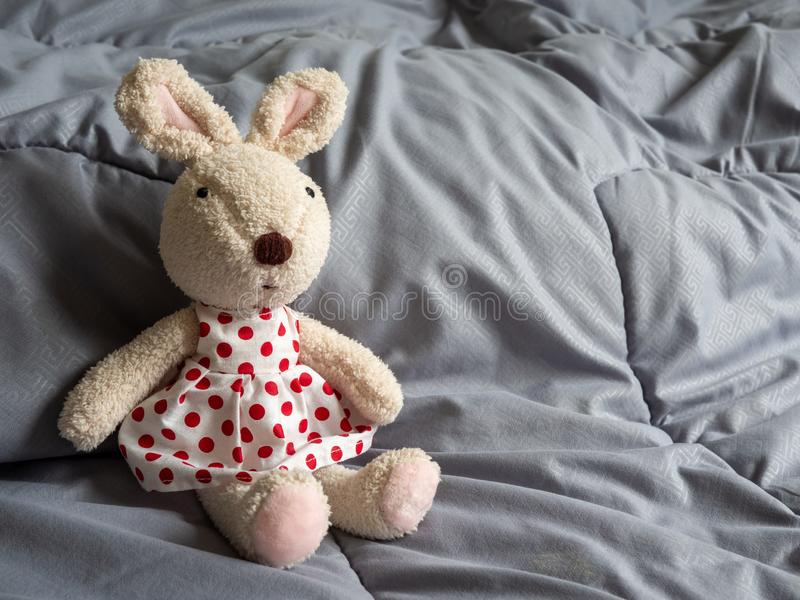 A rabbit doll wearing a red polka dot dress sitting on the bed stock photos