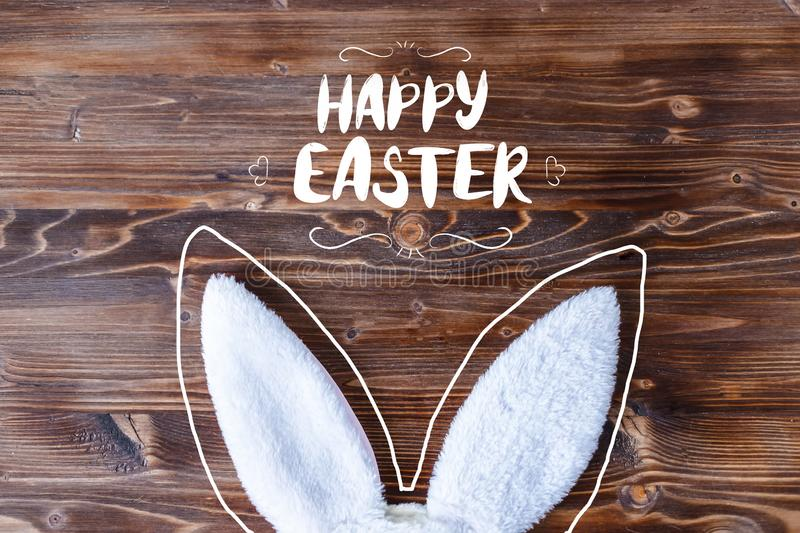 White rabbit ears with Happy Easter lettering inscription on a wooden background stock photos