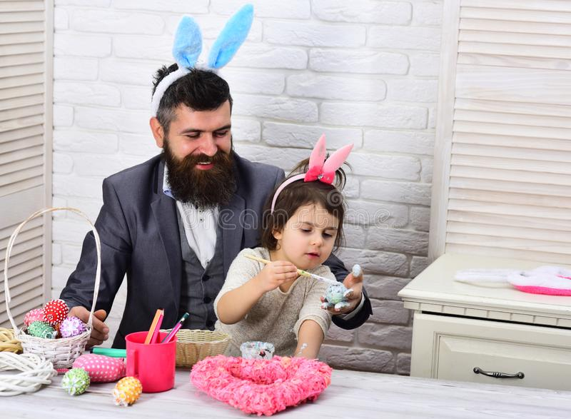 Rabbit family with bunny ears. father and daughter paint easter eggs. Egg hunt on spring holiday. Family love easter. Happy easter. Childhood. Easter is their royalty free stock images