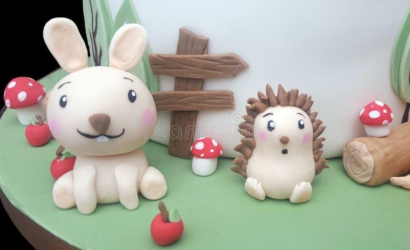 Rabbit and hedgehog sugar models. Kawaii rabbit and hedgehog sugar models on a woodland themed cake. With apples, mushrooms, toadstools and tree logs. Handmade stock images