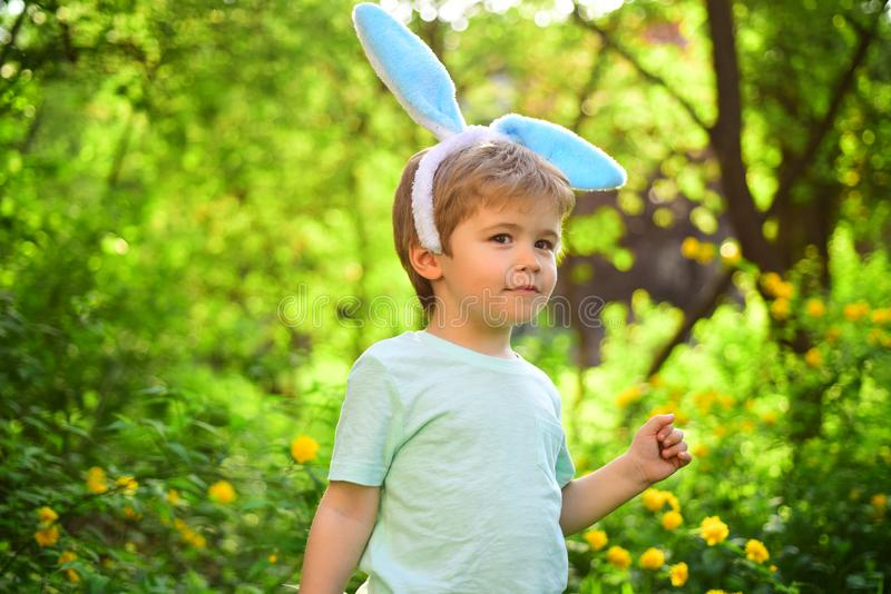 Rabbit kid with bunny ears. Hare. Egg hunt on spring holiday. love easter. Family holiday. Little boy child in green stock photo