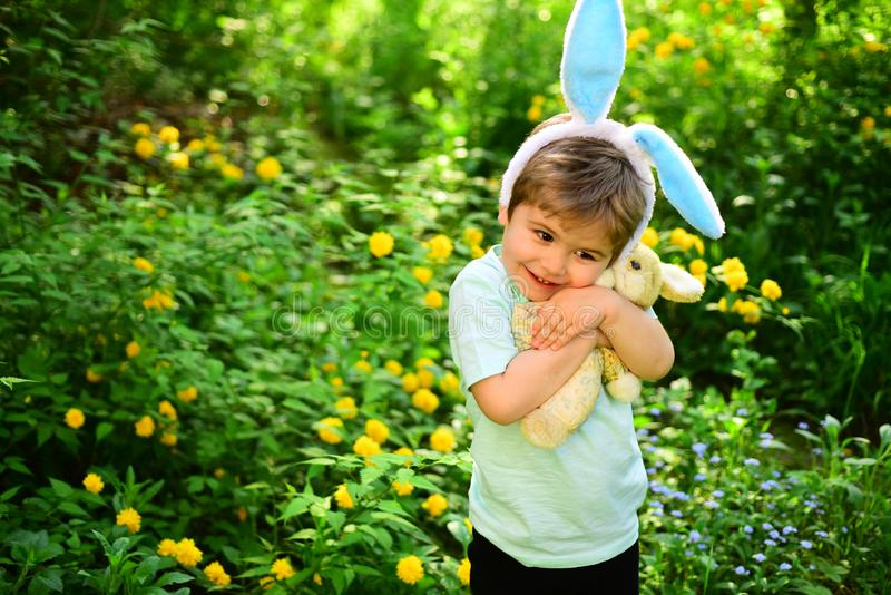 Rabbit kid with bunny ears. Hare toy. Egg hunt on spring holiday. love easter. Family holiday. Little boy child in green royalty free stock photography