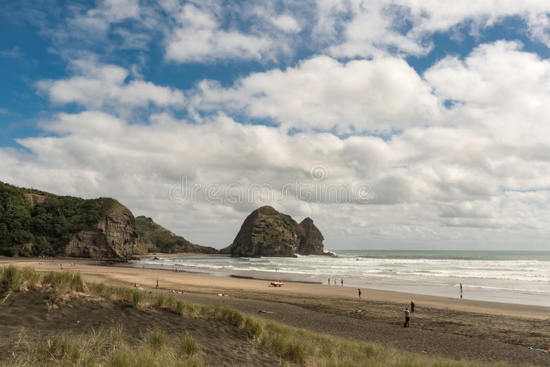Rabbit rock and Piha Beach seen from along the beach. Auckland, New Zealand - March 2, 2017: Rabbit rock and sandy Piha Beach under blue cloudy sky and royalty free stock images