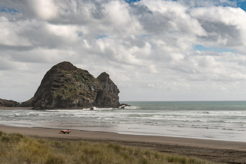 Rabbit rock at Piha Beach seen from along the beach. Auckland, New Zealand - March 2, 2017: Rabbit rock at sandy Piha Beach under stormy sky and surrounded by royalty free stock photos