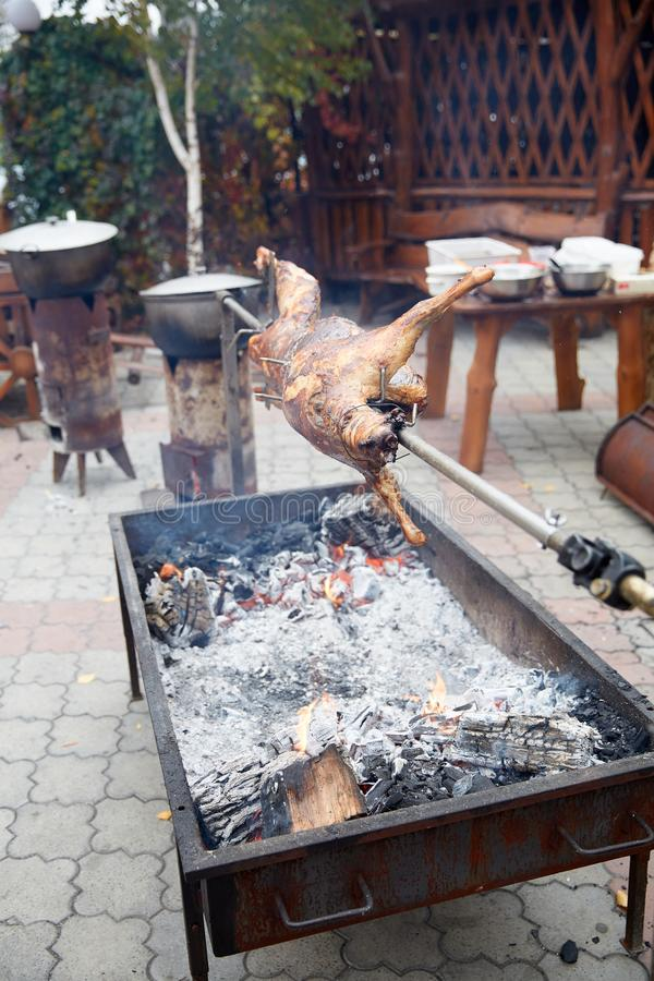 Rabbit on a spit on the grill roasts. Rabbit juicy cut on a spit on a grill roasted royalty free stock images