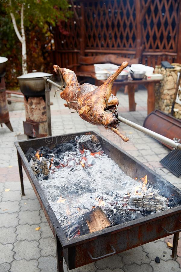 Rabbit on a spit on the grill roasts. Rabbit juicy cut on a spit on a grill roasted stock photos