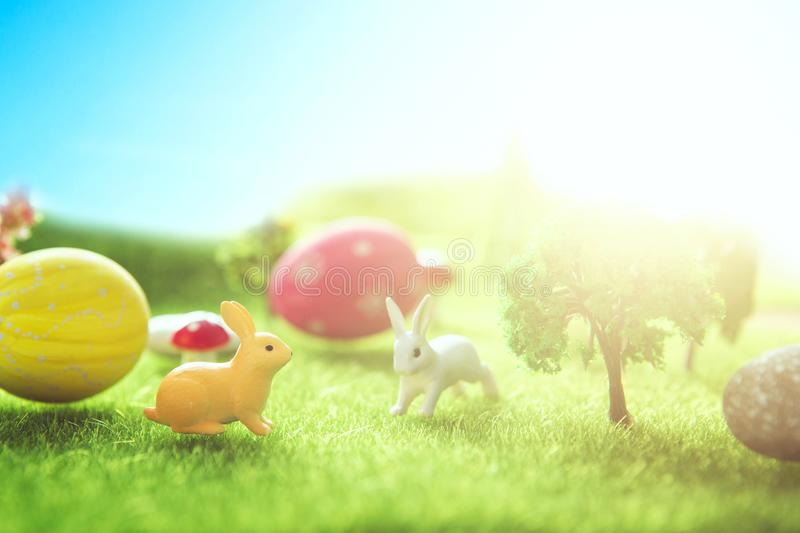 Rabbit toys with easter eggs on a meadow grass. Yellow easter egg spring meadow with two rabbit and easter eggs. Fairy tale stock photo