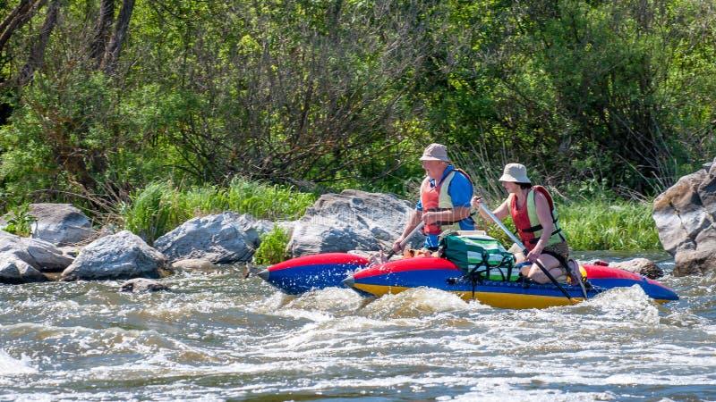 rabbiting Ett gift par åldrades segling på ett rubber uppblåsbart fartyg Vatten plaskar närbild ekologisk turism royaltyfri foto