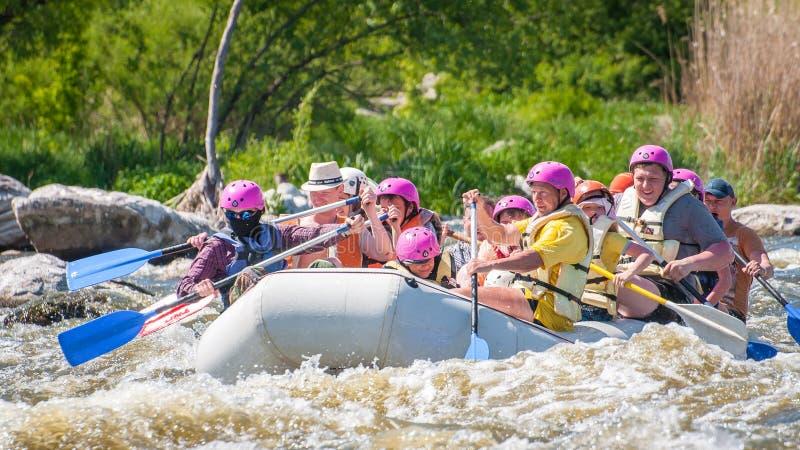 rabbiting Glat företag av folk av olika åldrar som seglar på ett rubber uppblåsbart fartyg Teamwork positiva sinnesrörelser royaltyfri bild