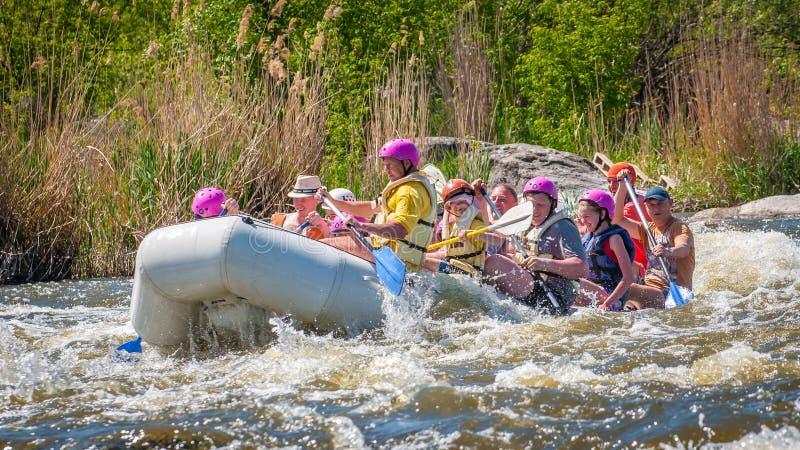 rabbiting Glat företag av folk av olika åldrar som seglar på ett rubber uppblåsbart fartyg Teamwork positiva sinnesrörelser royaltyfri foto