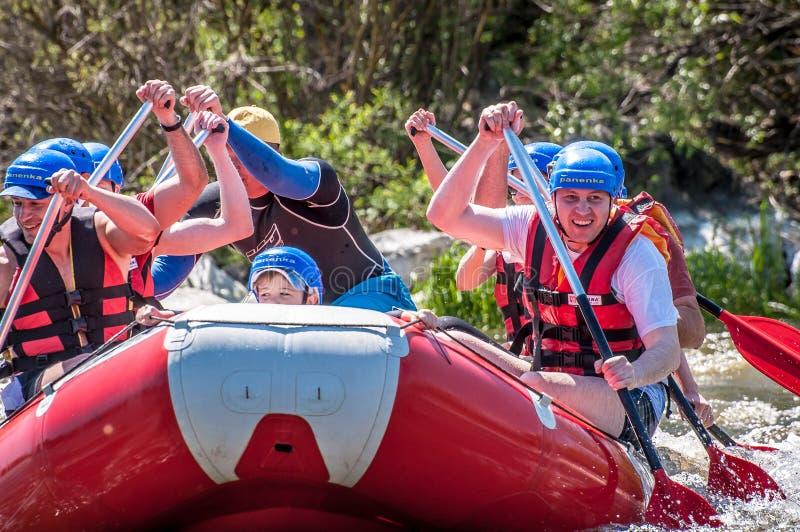 rabbiting Närbildsikt av åror med plaskande vatten En grupp människor med ett barn på ett rubber uppblåsbart fartyg fotografering för bildbyråer