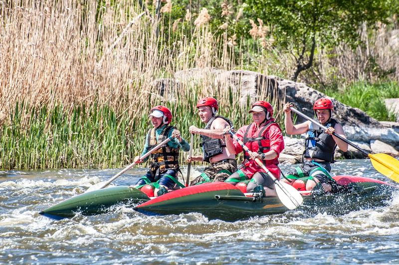 rabbiting Sikt av åror med plaskande vatten En grupp människor på ett rubber uppblåsbart fartyg i en stormig ström av vatten fotografering för bildbyråer