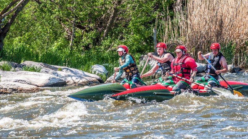 rabbiting Sikt av åror med plaskande vatten En grupp människor på ett rubber uppblåsbart fartyg i en stormig ström av vatten royaltyfria foton