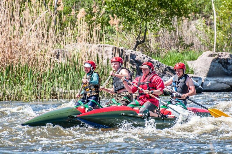 rabbiting Sikt av åror med plaskande vatten En grupp människor på ett rubber uppblåsbart fartyg i en stormig ström av vatten royaltyfri foto