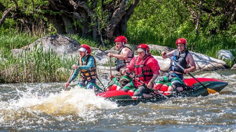 rabbiting Sikt av åror med plaskande vatten En grupp människor på ett rubber uppblåsbart fartyg i en stormig ström av vatten arkivfoto