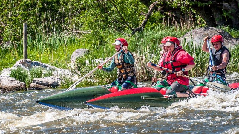 rabbiting Sikt av åror med plaskande vatten En grupp människor på ett rubber uppblåsbart fartyg i en stormig ström av vatten royaltyfri fotografi