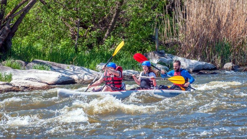 rabbiting Tre idrottsmän seglar på ett rubber uppblåsbart fartyg Teamwork Vatten plaskar närbild ekologisk turism arkivbild