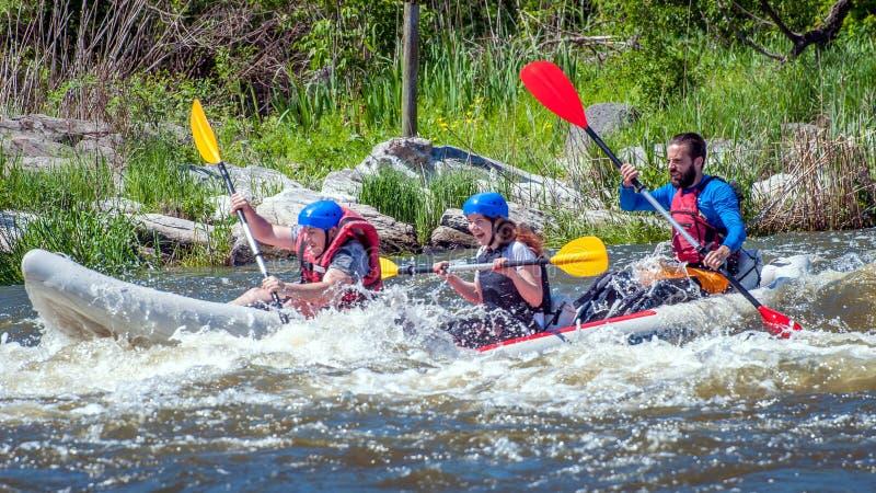 rabbiting Tre idrottsmän seglar på ett rubber uppblåsbart fartyg Teamwork Vatten plaskar närbild ekologisk turism arkivfoton
