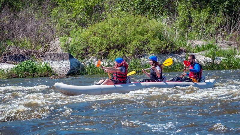rabbiting Tre idrottsmän seglar på ett rubber uppblåsbart fartyg Teamwork Vatten plaskar närbild ekologisk turism royaltyfri foto