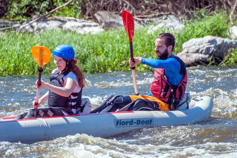 rabbiting Två idrottsmän seglar på ett rubber uppblåsbart fartyg i en ström för kokande vatten Vatten plaskar närbild royaltyfria foton