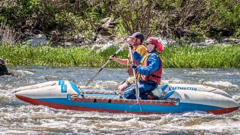rabbiting Ung gift parsegling på ett rubber uppblåsbart fartyg i en stormig ström av vatten Vatten plaskar närbild royaltyfri foto