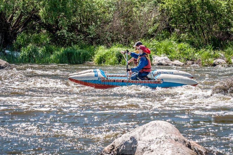 rabbiting Ung gift parsegling på ett rubber uppblåsbart fartyg i en stormig ström av vatten Vatten plaskar närbild royaltyfri fotografi