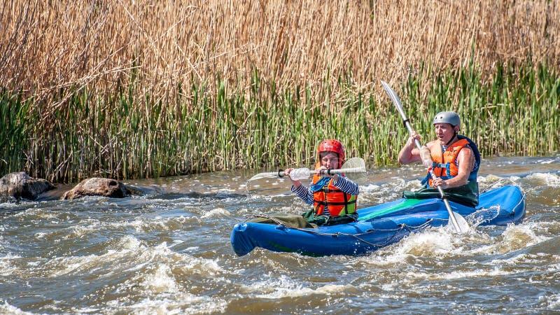 rabbiting Ung gift parsegling på ett rubber uppblåsbart fartyg i en stormig ström av vatten Vatten plaskar närbild royaltyfri bild