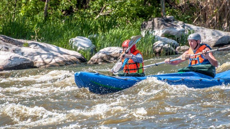 rabbiting Ung gift parsegling på ett rubber uppblåsbart fartyg i en stormig ström av vatten Vatten plaskar närbild royaltyfria foton